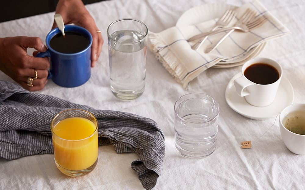 A breakfast table with drinking glasses, a mug and teacup.