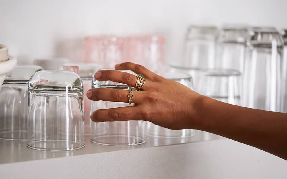 A person placing a drinking glass on a shelf.