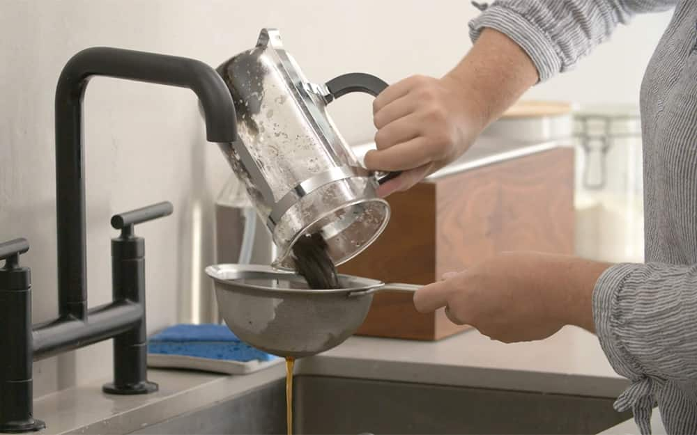 A person straining used coffee grounds from a french press coffee maker.