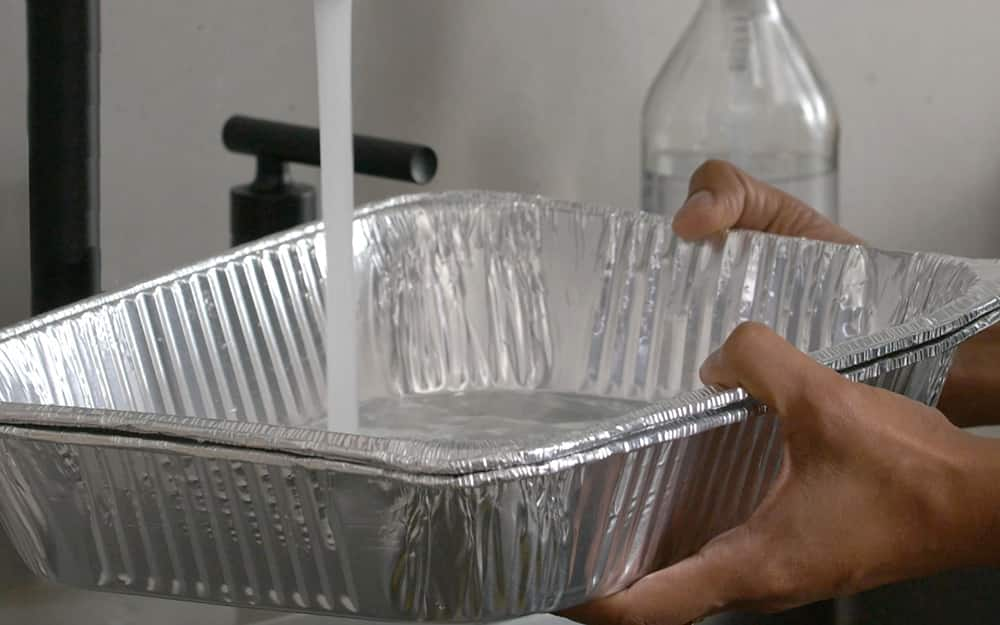 A person filling a pan with water.