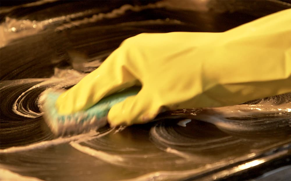 A person scrubbing a treated surface in the oven.