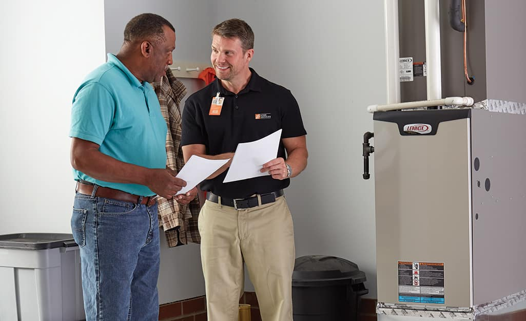 A homeowner talking to a Home Depot associate next to a furnace.
