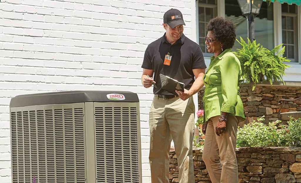 A Home Depot associate with a homeowner next to an air conditioner outside a home.