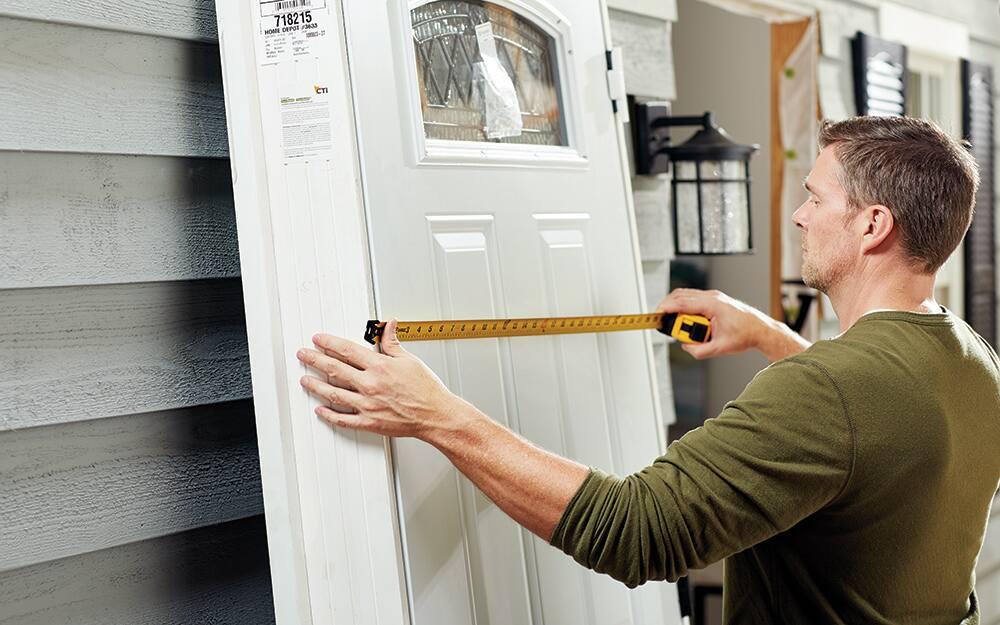A man measuring an entry door