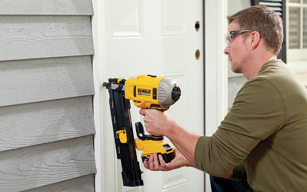 A man securing a new entry door outside the home.