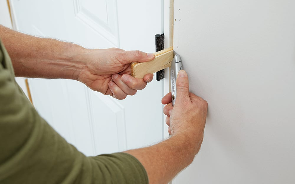 A man anchoring moulding inside the home.