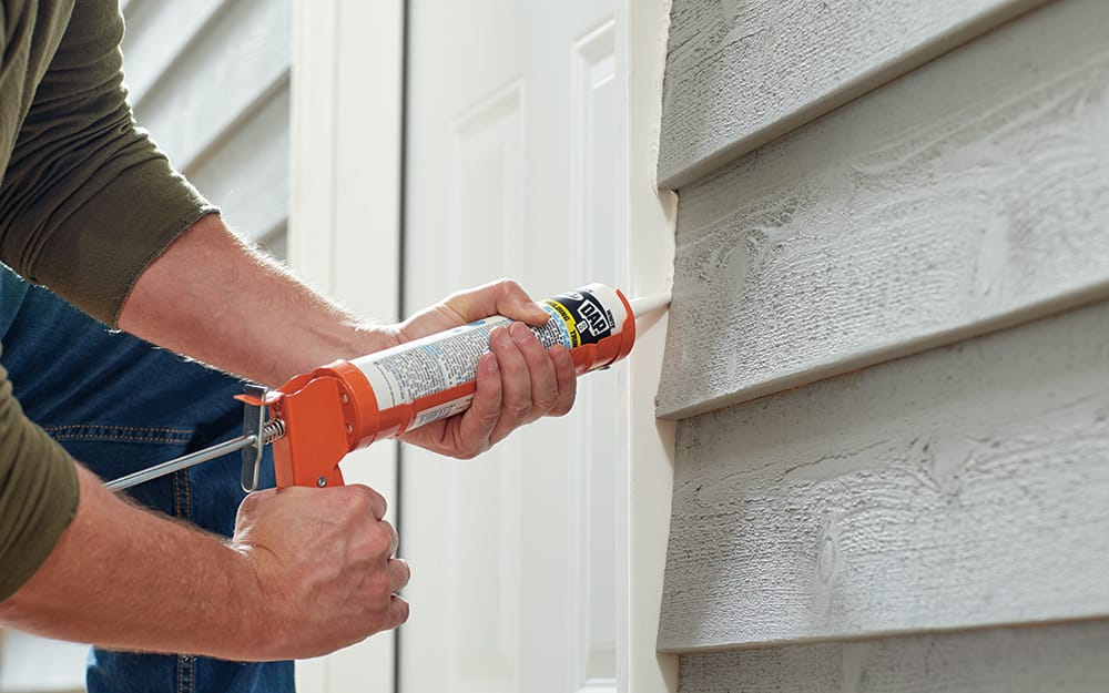 A man caulking the exterior of a new entry door.