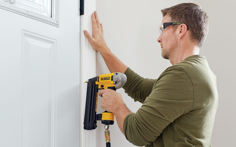 A man nailing trim on a new entry door.