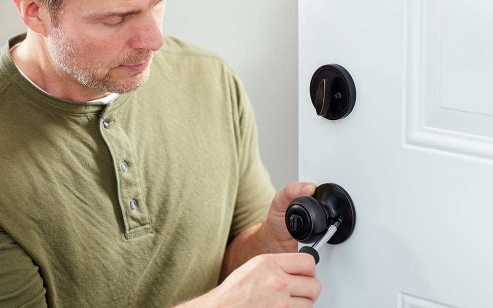 A man installing a door knob and safety lock on a new entry door.
