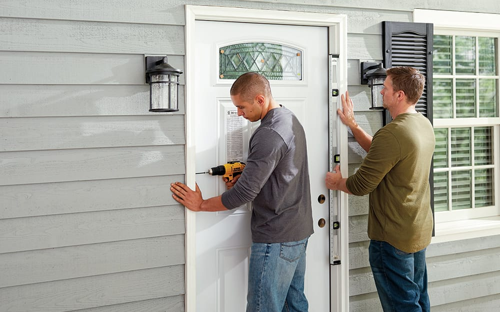 Two men securing a new entry door on the exterior of a home.