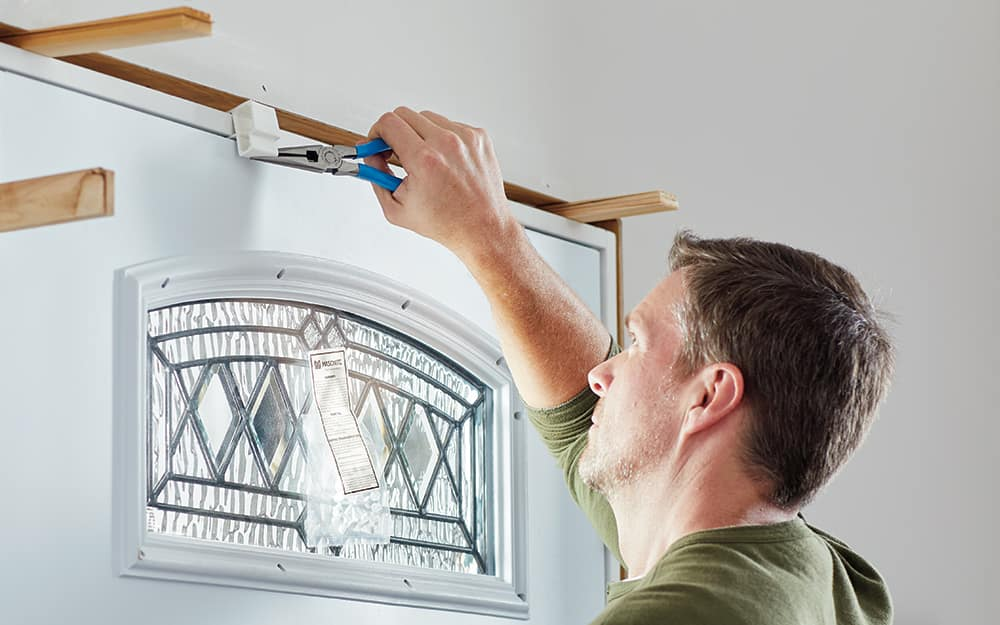 A man applying shims to a new entry door inside the home.