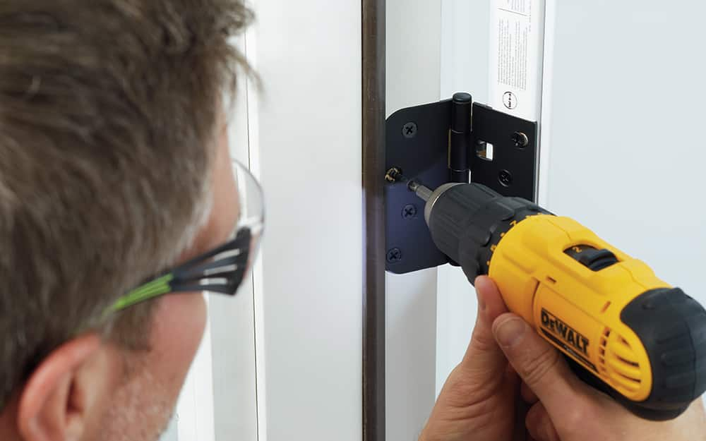 A man drilling hinges into a new entry door inside the home.