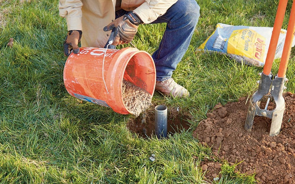 A person setting the ground sleeve of a flag pole with concrete
