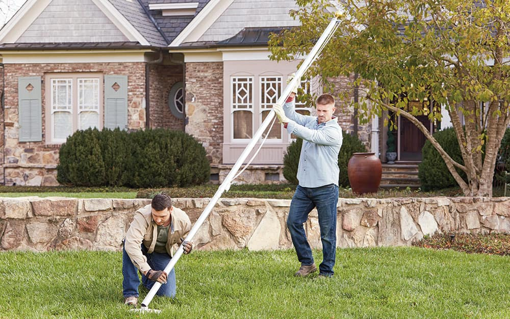 Two people installing a flag pole into the hole