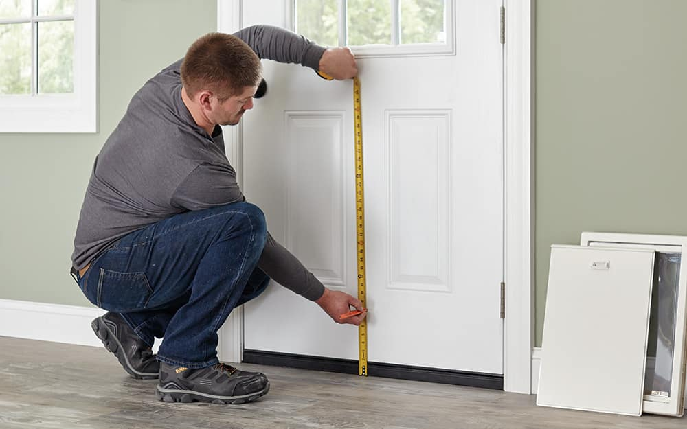 A man measuring the bottom of an exterior door