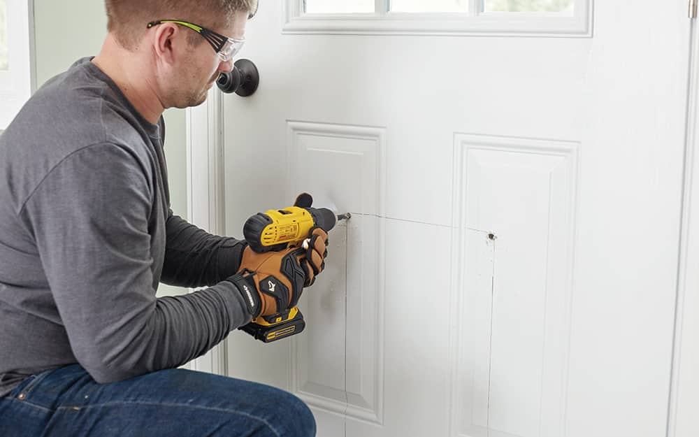 A man drilling holes into the bottom of an exterior door