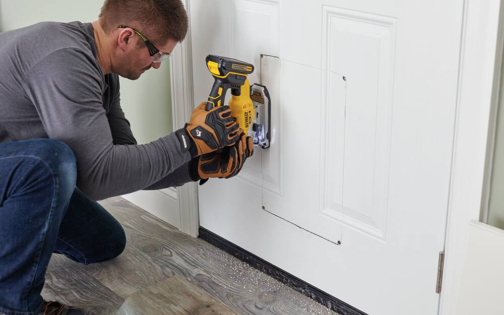 A man cutting into the bottom of an exterior door