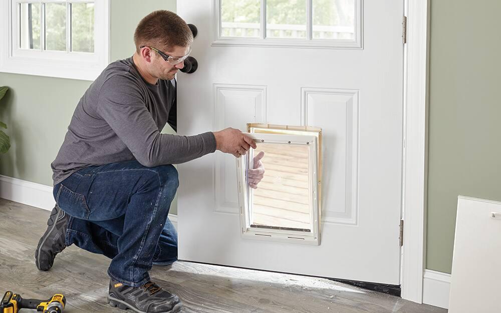 A man placing the frame of a dog door into an exterior door