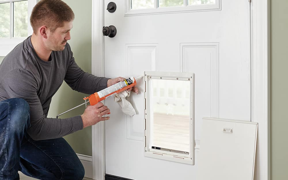A man sealing the frame of a dog door into an exterior door