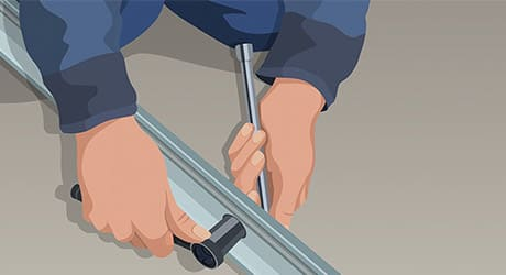 A person uses a socket wrench to assemble a garage door opener carriage tube.