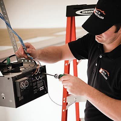 A person stands on a step ladder and installs the motor of a garage door opener.