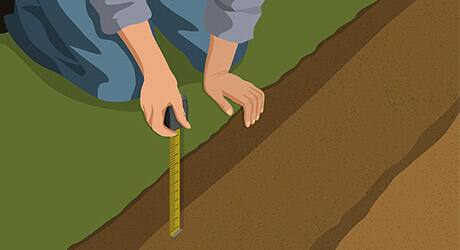 A person measuring the depth of a trench.