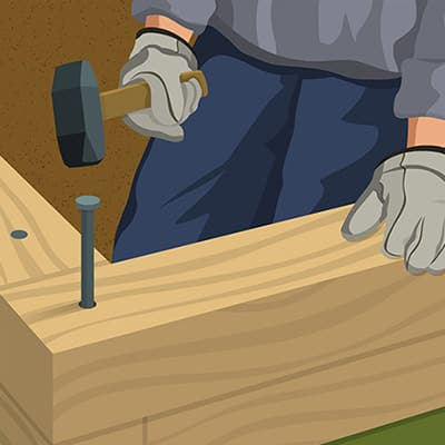 An illustration of a person driving a spike through timber garden edging.