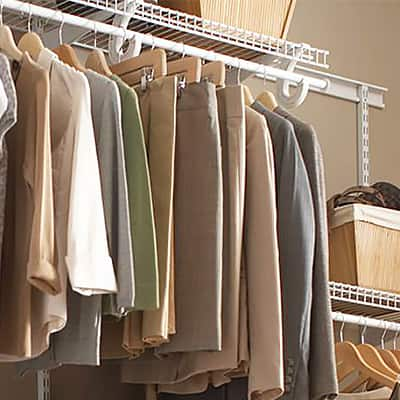 Clothes hang from a wire closet shelving system.
