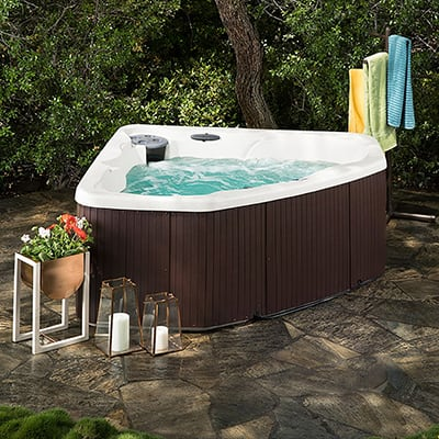 A bubbling hot tub sits on a shady patio.