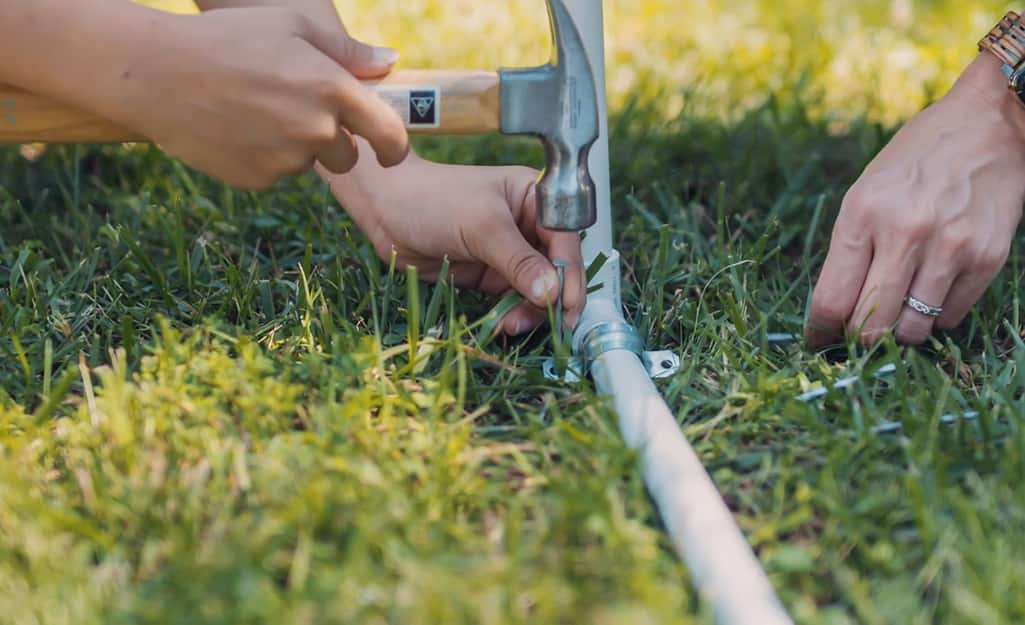 A person anchoring a DIY kids sprinkler to a lawn with a U-bolt.