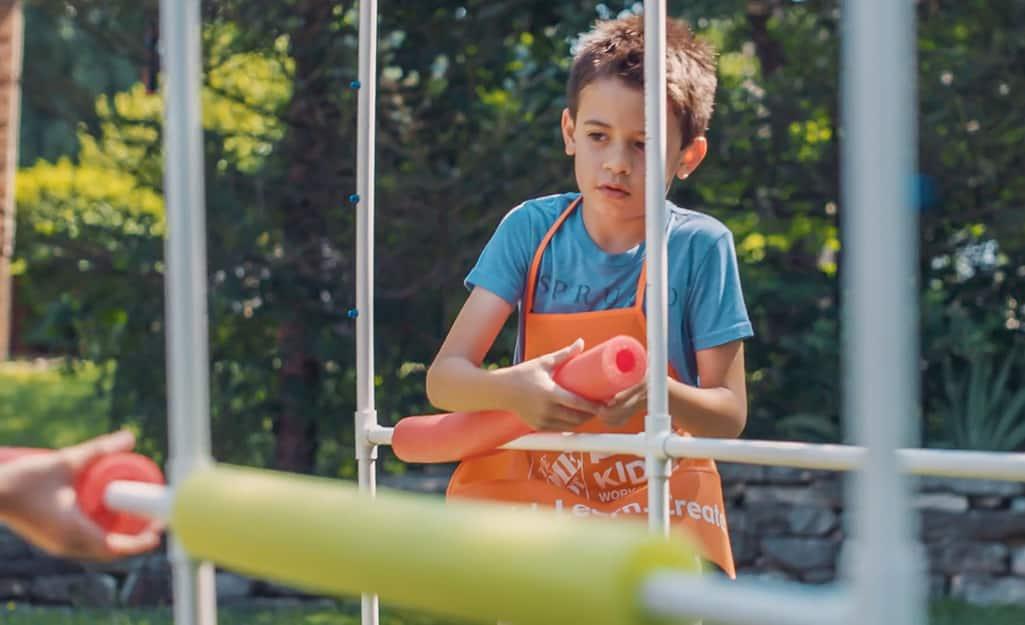 A child placing pool noodle bumpers on a DIY kids sprinklers.