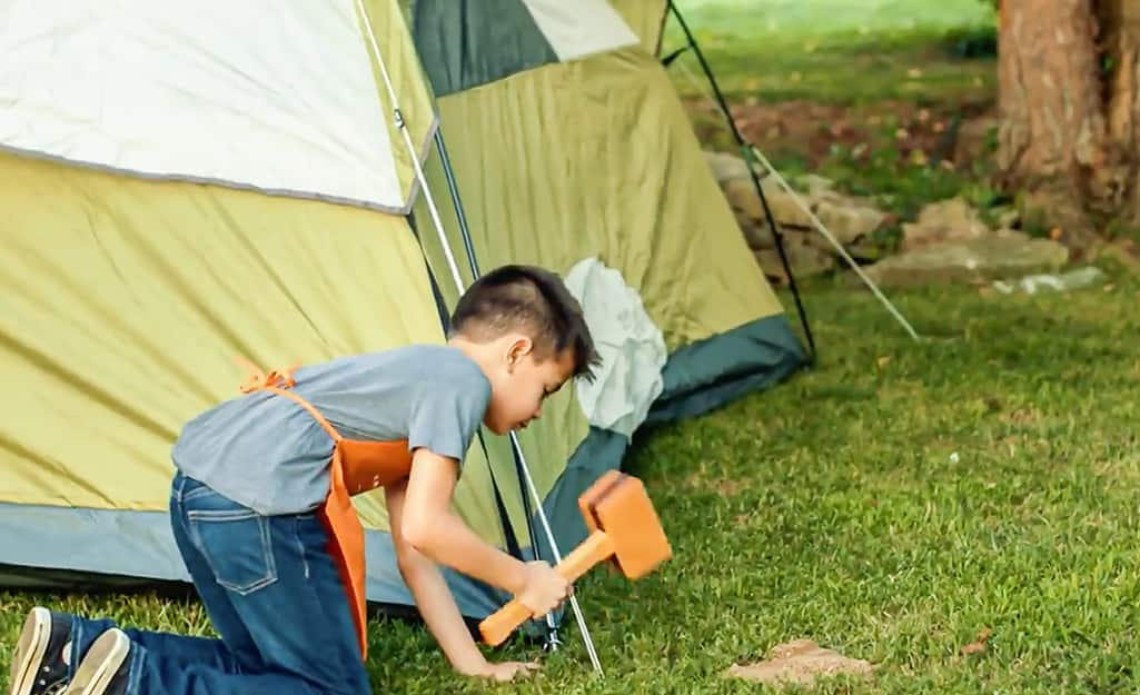 Kid hammers in the sides of the tent.