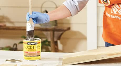 a person stains a piece of wood