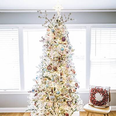 A decorated Christmas tree sits on hardwood floors in front of a wall of windows.