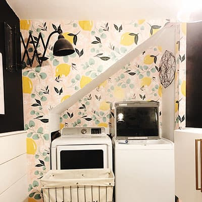 A laundry room with a colorful accent wall and white appliances.