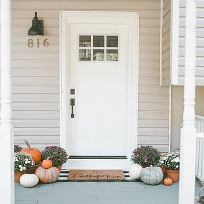A front entryway with a white door decorated with pumpkins for Fall.