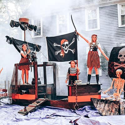 Three children dressed as pirates stand on a pirate ship.