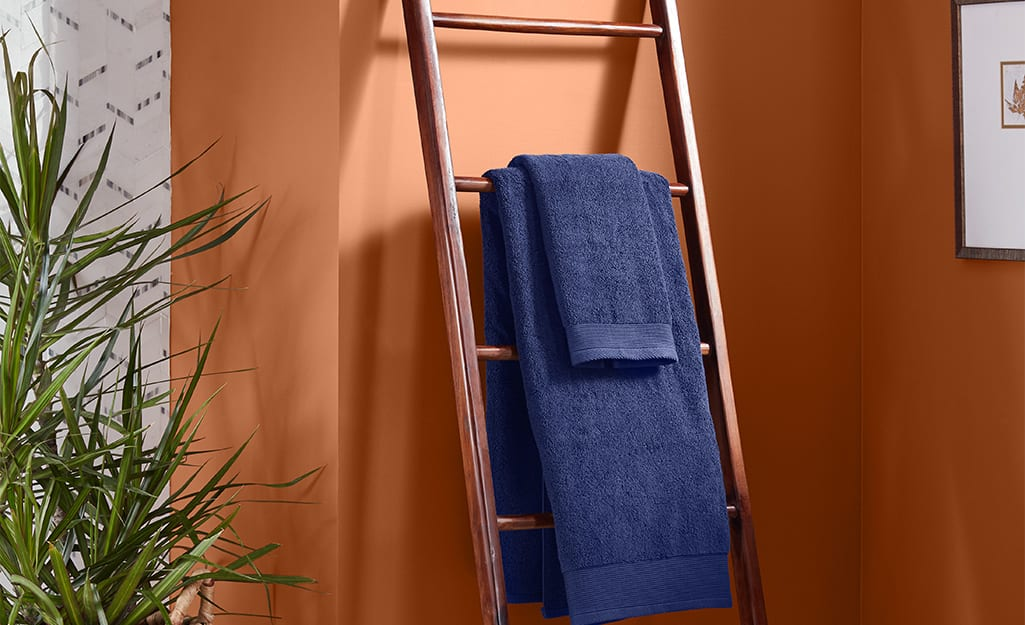 Leaning storage ladder with a blue towel on it, leaning against an orange wall.