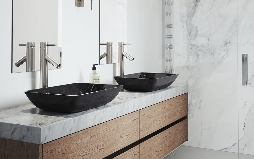 A bathroom features a double vanity with black vessel sinks on a stone countertop
