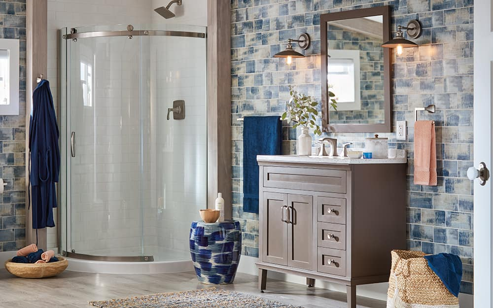 A bathroom features a blue and gray patterned wall tile, gray vanity and a walk-in shower with a curved glass door