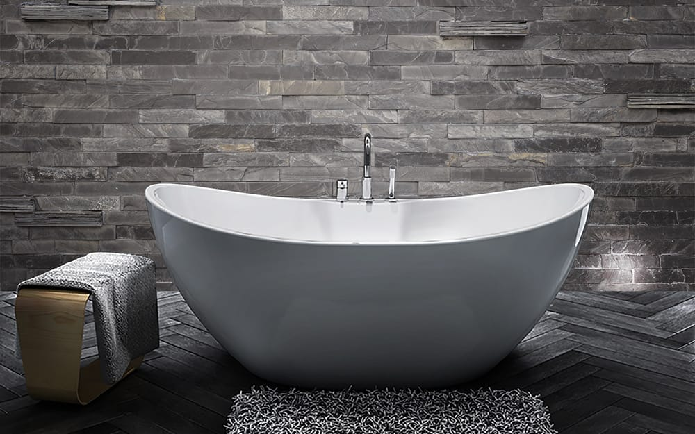 A white freestanding tub with curved sides sits in front of a wall with gray stone tile