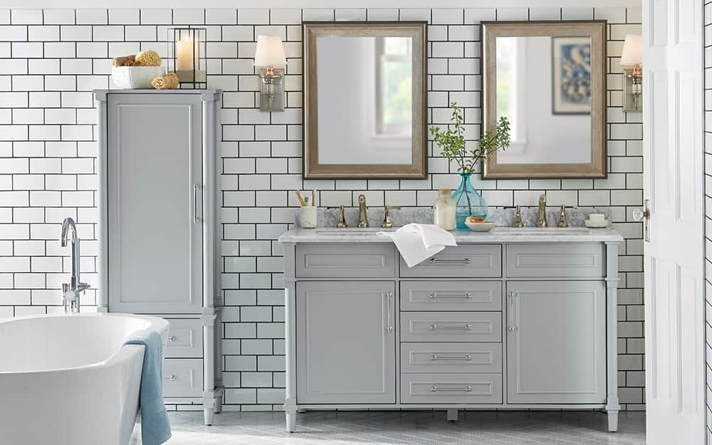 A bathroom features a freestanding tub, double vanity with matching gray upright storage cabinet and a tiled wall
