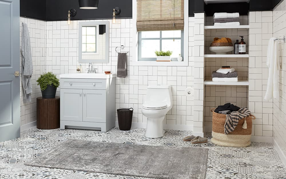 A bathroom features white wall tile and black and white mosaic floor tile