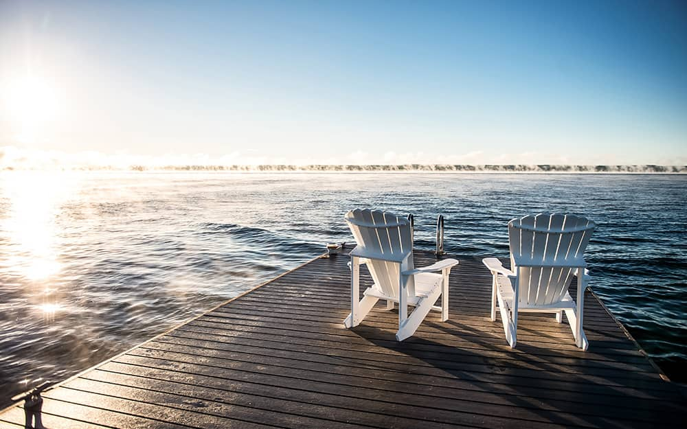 Two chairs on a wooden dock at a lake.
