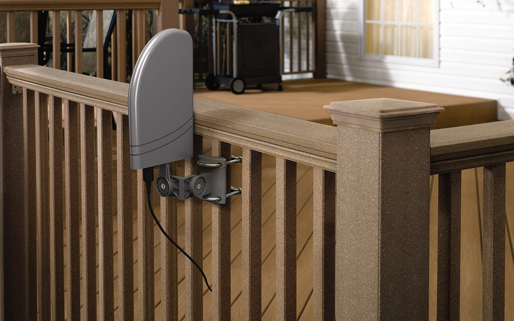 An outdoor amplified HD antenna is attached to the railing of a deck.