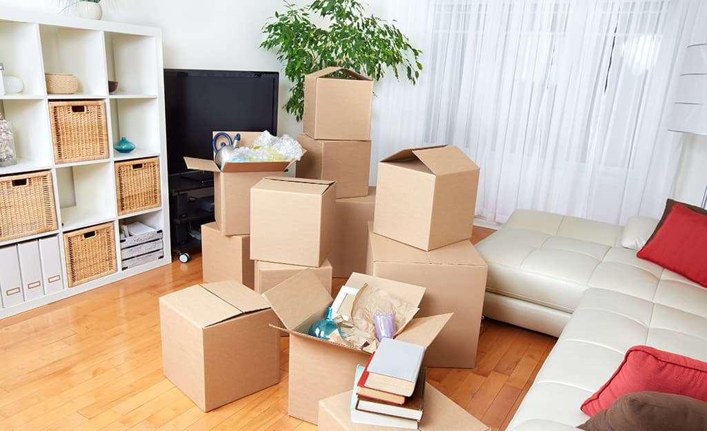 A variety of cardboard moving boxes in a living room.