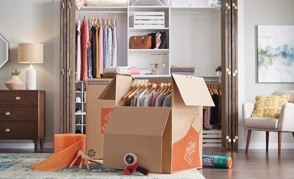 The Home Depot cardboard wardrobe boxes being packed in a bedroom.