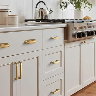 Gold handles and pulls installed on white cabinetry.
