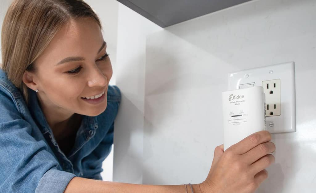 A person plugging in a carbon monoxide detector.
