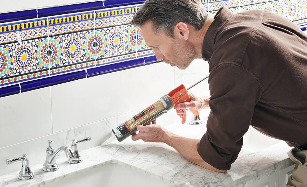 A man using a caulk gun to seal a bathroom counter.